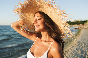 Photo of positive brunette woman in swimsuit and straw hat smiling and sunbathing while walking by seaside Wall mural