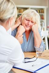 Ärztin tröstet weinende Patientin in Sprechstunde