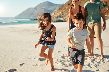 Happy young white family on holiday exploring a beach together, front view, full length, crop