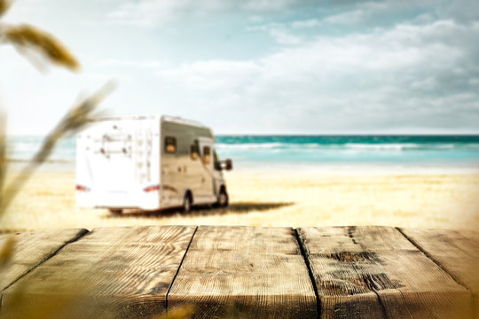 Table background with a wooden board and sunny beach and ocean and a camper van