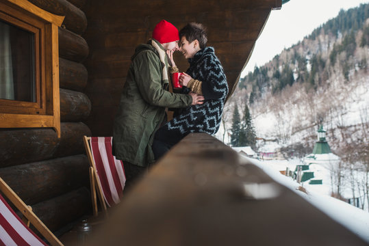 Happy stylish couple have fun on the wooden chalet terrace outdoor. Drinkind tea in winter vacation