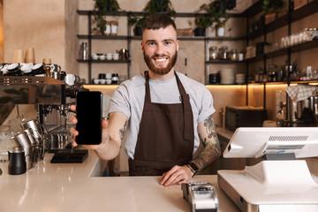 Fototapeta Smiling attractive man barista standing obraz