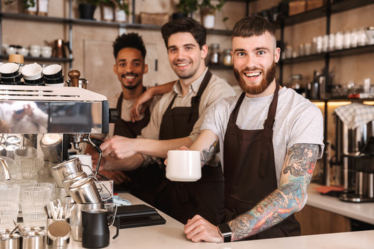 Three cheerful male baristas standing at the coffee shop