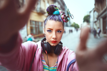 Playful cool funky hipster young girl with headphones and crazy hair taking selfie on street