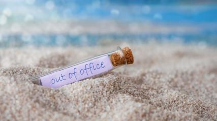 Out of office- Flaschenpost im Sand-Konzept Urlaub