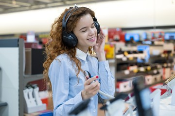 Spoed Foto op Canvas Muziekwinkel Red-haired girl standing in front of the stand in the electronics store listening to music in headphones