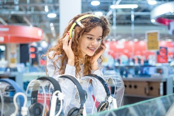 Foto op Plexiglas Muziekwinkel Red-haired girl standing in front of the stand in the electronics store chooses headphones before buying wearing on her head listening to the sound