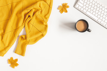 Autumn composition. Cup of coffee, yellow sweater, maple leaves on white background. Autumn, fall concept. Flat lay, top view, copy space