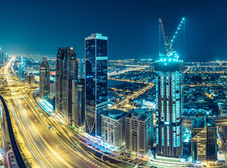 Downtown Dubai at night. Scenic aerial view on highways and skyscrapers.