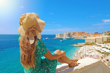 Beautiful young woman sitting on wall looking at stunning view of Mediterranean sea and Dubrovnik old town in Croatia, Europe. Lifestyle woman with straw hat wearing green dress enjoy landscape view.