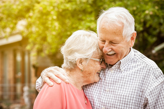 older couple are standing in the garden, hugging each other and laughing at each other