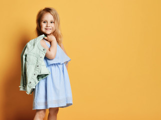 Full length portrait of a cute little child girl in a stylish dress and denim.