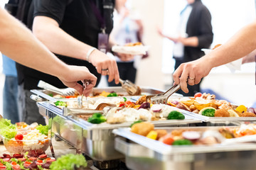 Hands picking up food from buffet catering table at the party.