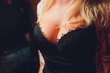 Decollete, female breast. Neckline black dress and fur collar.