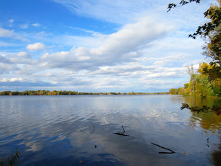 Beautiful blue sky with white clouds and a calm lake and the color of Fall