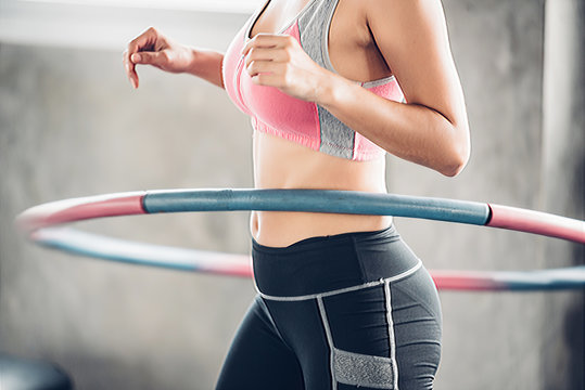 Asian woman excercise with hula hoop in the gym.