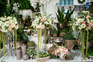 Foto auf Leinwand Blumen Many flowers and candles on table in florist shop, copy space. Small business. Floral design studio, luxury wedding decorations. Flowers delivery. Holiday and floristry concept