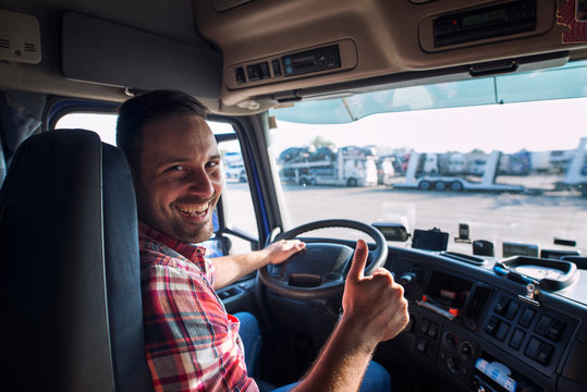 Portrait of truck driver sitting in his truck holding thumbs up. Transportation and trucking services.