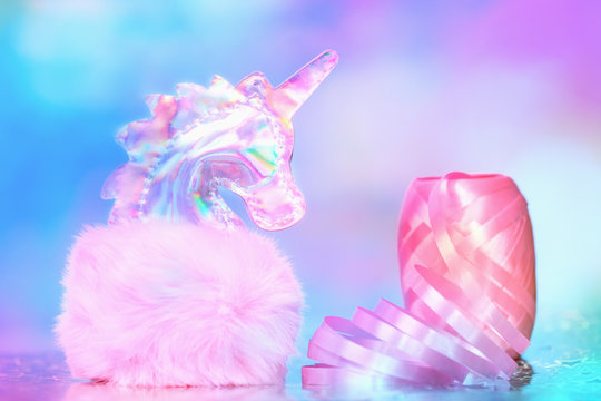 Shiny zine type gradient holographic iridescent head of pink soft fluffy toy unicorn on bright blue pink bokeh fluorescent neon background. Celebration birthday greeting card concept with copy space