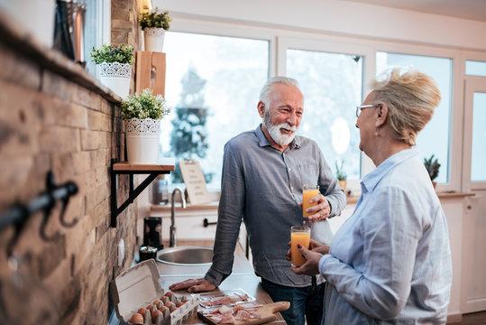 Senior couple in the morning drinking orange juice and preparing breakfast.