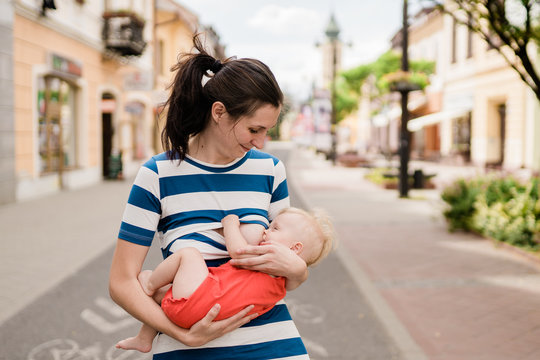 young brunete mother breast feeding baby girl outdoors in public town