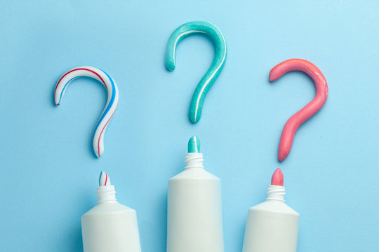 Question mark from toothpaste. Concept of choosing good toothpaste for teeth whitening. Tube of colored toothpaste on blue background. Copy space for text.