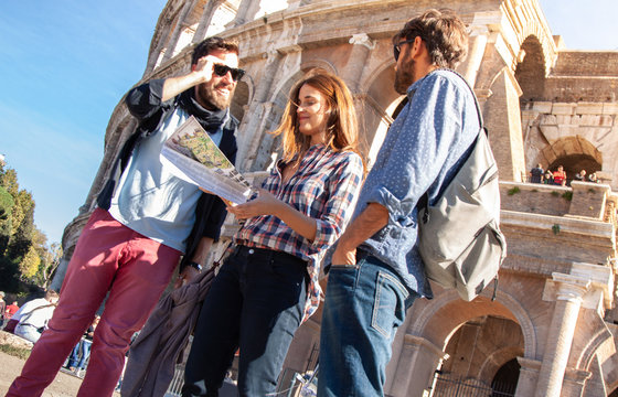 Three happy young friends tourists standing in front of colosseum in rome reading city map guide