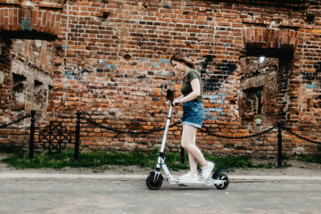 Electric scooter for a girl in the city. eco-friendly transport is an alternative to a car in the city, combating traffic congestion. Wall mural