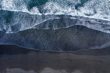 Aerial view of Atlantic ocean waves washing black sandy beach
