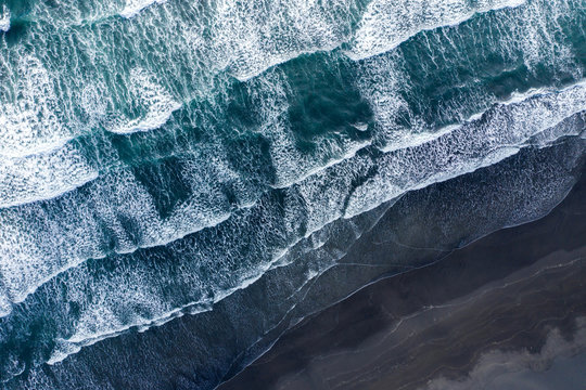 Aerial view of Atlantic ocean waves washing black sandy beach