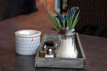 Zuckerstreuer, Aschenbecher und Tischdekoration