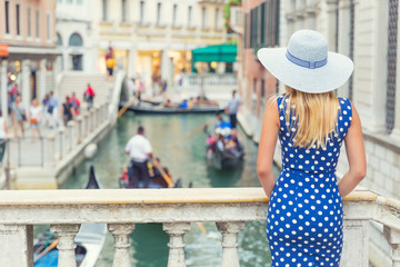 Happy young attractive woman fashion model of venice italy in blue polka dot outfit