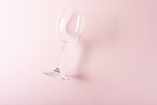 Single empty wineglass lying on pink background. Wine degustation concept. Flat lay. Top view. Copy space