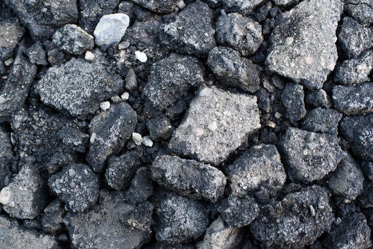 Pieces of asphalt pavement in the hole in the road
