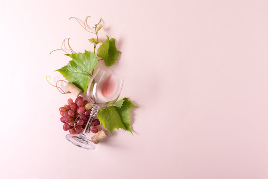 Single wineglass with rose wine, grape, leaves and cork lying on pink background. Wine degustation concept. Flat lay. Top view. Copy space