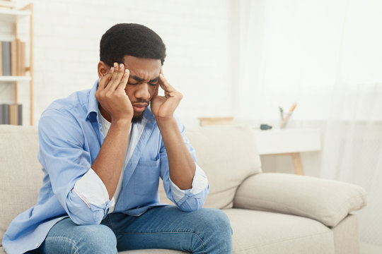 African-american man suffering from headache at home