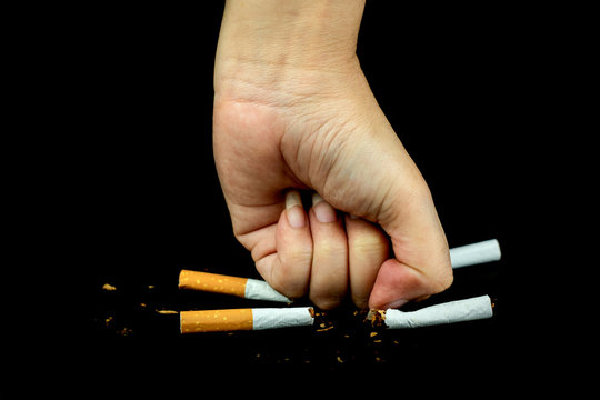women fist crushing cigarettes over black Background
