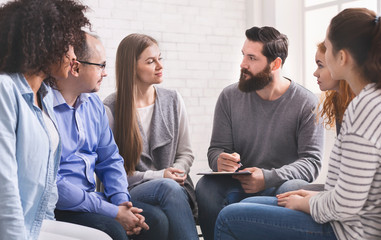 Psychologist asking members of rehab group about their addictions