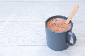 Hot chocolate in a blue-grey ceramic mug with wooden stirrer isolated on white painted wood. Space...