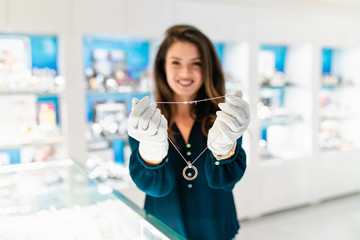 Beautiful middle age woman working in jewelry store. She holding and showing expensive necklace and earrings to male buyer.