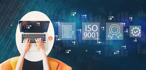 Wall Mural - ISO 9001 with person using a laptop on a white table