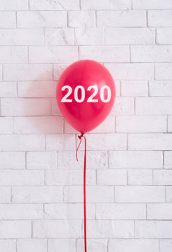 Red balloon with 2020 concept in front of white bricks wal