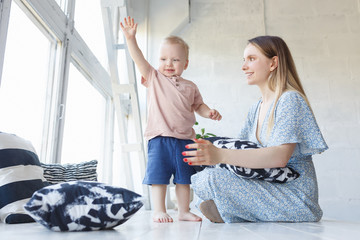 Side view of cheerful woman holding baby boy in her hands and looking at him with love sitting on wooden white floor over big window at home. Young beauty mom spending morning with two-year old son
