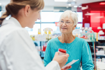 Poster Apotheek Senior woman in pharmacy talking to the chemist or pharmacist