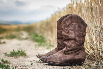 Cowboy boot on dirt road next to wheat field