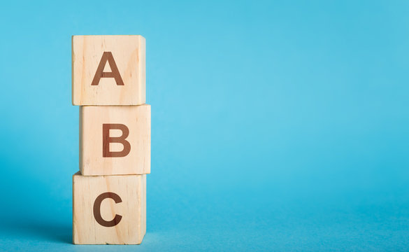 ABC letters of wooden blocks in pillar form on blue background