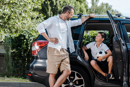 happy father standing with hand on hip near car and looking at son with football
