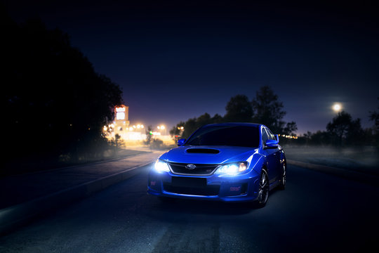 Moscow, Russia - June 18, 2016: Blue car Subaru Impreza WRX STI is parked on asphalt countryside road near city and forest at moon night