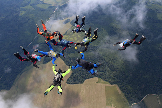 Skydiving. A group of skydivers is in the sky.