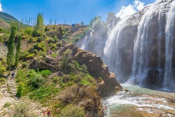 Tortum (Uzundere) waterfall from the side with people in Uzundere, Erzurum, Turkey
